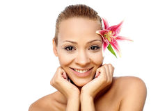 Smiling girl with pink flower Royalty Free Stock Image