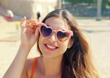 Smiling girl in pink heart lolita sunglasses on the beach. Holidays, vacation travel and freedom concept.  stock photography