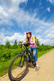 Smiling girl in pink helmet ready to ride a bike Stock Photography