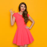 Smiling Girl In Pink Mini Dress Showing Ok Sign. Smiling beautiful young woman in pink mini dress posing with hand on hip and showing ok hand sign. Three quarter Stock Photo