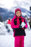Smiling girl in pink ski suit making snowball Royalty Free Stock Photo