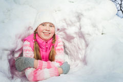 Smiling girl in pink wear laying at the snow hole Royalty Free Stock Photography