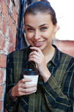 Smiling girl in a plaid green shirt standing disposable coffee cup Stock Images