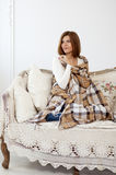 Smiling girl with plaid on sofa Stock Images