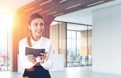 Smiling girl with a planer in an office Royalty Free Stock Image