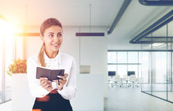 Smiling girl with a planer in an office toned Royalty Free Stock Photo