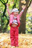 Smiling girl playing in autumn park Royalty Free Stock Image