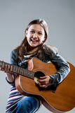 Smiling girl playing classic acoustic guitar Stock Photography