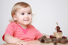 Smiling girl playing with cones and chestnuts Royalty Free Stock Photography