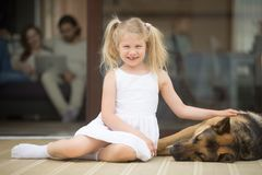 Smiling girl playing with dog outside house looking at camera. Smiling girl playing with dog outside country house looking at camera, little kid stroking Stock Images