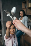 Smiling girl playing with father using spoons in kitchen Royalty Free Stock Image