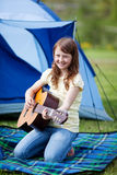 Smiling Girl Playing Guitar Against Tent Royalty Free Stock Photo