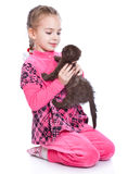 A smiling girl is playing with a kitten Stock Images