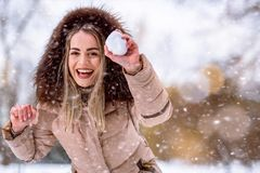 Girl playing snowball fight on the winter snow day. Smiling girl playing snowball fight on the winter snow day stock image