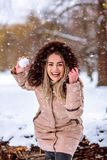 Smiling girl playing snowball fight on the winter snow day. Smiling young girl playing snowball fight on the winter snow day stock photo
