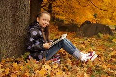 Smiling girl playing on the tablet in the park Royalty Free Stock Photo