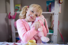 Smiling girl playing with a teddy bear and toy kitchen set royalty free stock photo