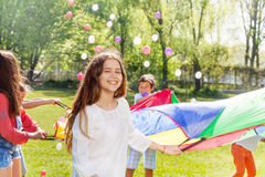Smiling girl playing together active game outdoors Stock Image
