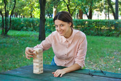 Smiling girl is playing a wooden block game Stock Photos