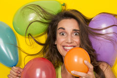Smiling girl plays with colorful baloons Stock Photos