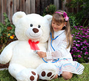 Smiling girl plays the doctor with huge toy white bear Royalty Free Stock Images