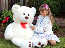 Smiling girl plays the doctor with huge toy white bear Royalty Free Stock Photos
