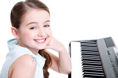 Smiling girl plays on the electric piano. Stock Photo