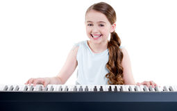 Smiling girl plays on the electric piano. Royalty Free Stock Image