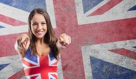 Smiling girl pointing at camera. And wearing a British flag tank top Royalty Free Stock Photos