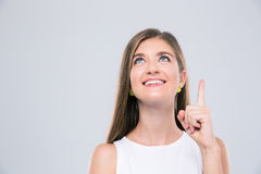 Smiling girl pointing finger up at copyspace Stock Photography