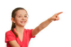 Smiling girl pointing forward. A smiling girl in red is pointing forward; isolated on the white background Stock Photo