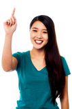 Smiling girl pointing upwards Royalty Free Stock Images