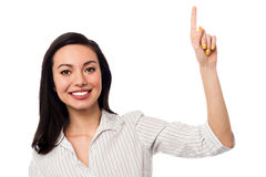 Smiling girl pointing upwards Stock Photography