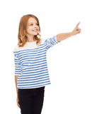 Smiling girl pointing at virtual screen Royalty Free Stock Image