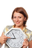 Smiling girl points a finger at clock Royalty Free Stock Photography