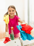 Smiling girl polishing mirror at bathroom while cleaning house Royalty Free Stock Photography