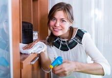 Smiling girl polishing shelves  in living room Stock Photos