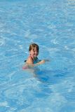 Smiling girl in the pool with blue water Royalty Free Stock Photos