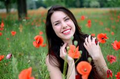 Smiling girl with poppies Stock Image