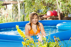 Smiling girl posing in the blue inflatable pool Stock Image