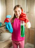 Smiling girl posing with cloth and cleanser spray at bathroom Royalty Free Stock Photography