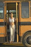 Smiling girl posing in front of an old school bus in the Valle de Vi�ales, in central Cuba Royalty Free Stock Images