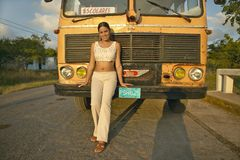 Smiling girl posing in front of an old school bus in the Valle de Vi�ales, in central Cuba Stock Photo