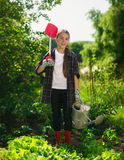Smiling girl posing at garden with spade and watering can Stock Image
