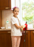 Smiling girl posing on messy kitchen with broom and scoop Royalty Free Stock Images