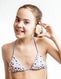 Smiling girl posing with seashell next to ear Stock Photography