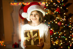 Smiling girl posing with shining gift box against Christmas tree Royalty Free Stock Image