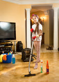 Smiling girl posing with vacuum cleaner while doing cleaning Stock Photo