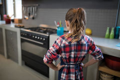 Smiling girl posing wearing an apron in the kitchen Stock Photography