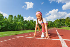 Smiling girl in position on knee ready to run Stock Image